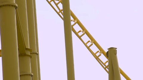 Inverted roller coaster moving fast down first drop.