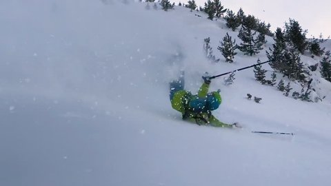 Extreme male skier riding off piste jumps and crashes into the fresh powder snow covering the mountain. Active tourist on vacation skiing in the freshly fallen snow slams and rolls down the hill.