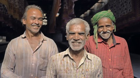 Mid shot of Laborers or old men working in the textile printing industry smiling. Three happy elderly daily wage workers laughing in front of the camera standing in the bed sheet printing factory