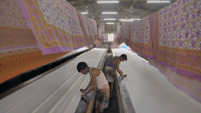 A moving shot of a daily wage workers or laborers working in textile printing interior factory setup while colorful printed cotton sheets hanged on the top to let them dry | Shutterstock HD Video #1017820066