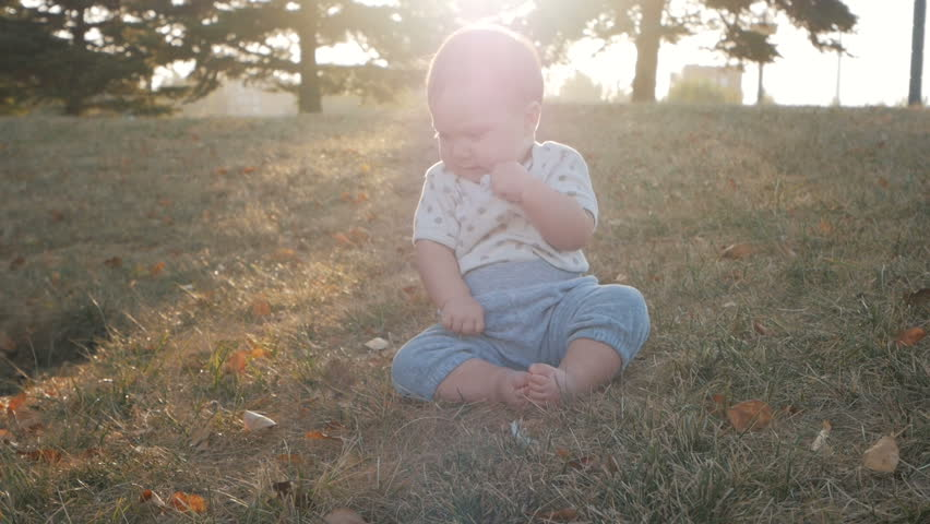 Small baby girl sitting on grass in park. Beautiful infant baby girl portrait in nature
