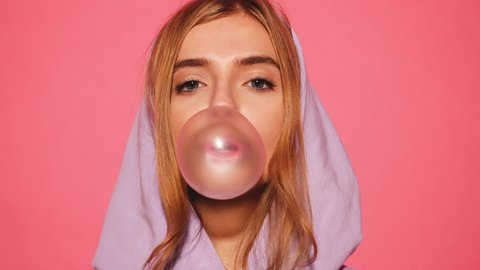 Portrait of young sexy playful blond girl dressed in blue hoodie standing and isolated over pink background blowing bubblegum candy bubbles and chewing gum. Woman looking at camera. 4k. Slow motion