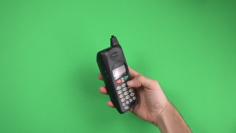Vintage 80s 90s cell phone with antenna on green screen chroma key