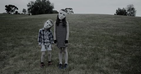 young children wearing a white halloween masks stand creepily and then scarily walk slowly towards the camera