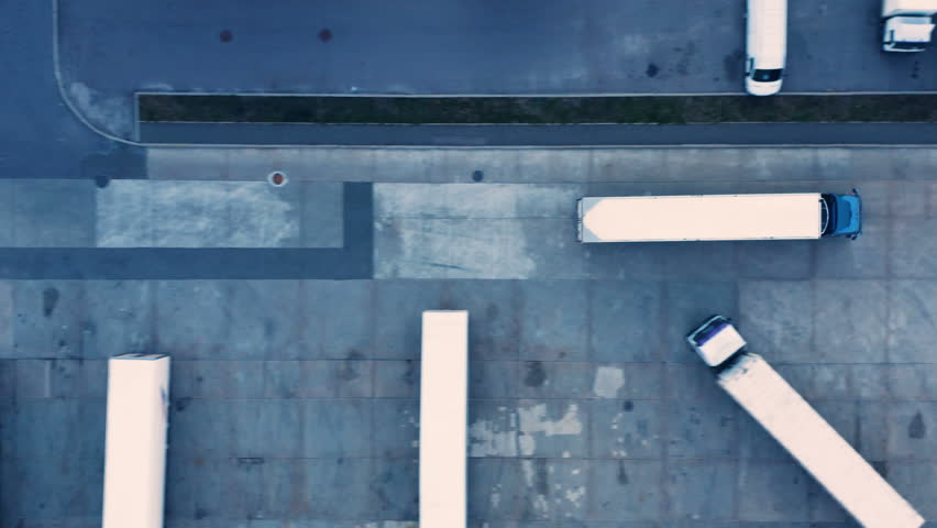 Aerial top view of a of semi-trailer truck traveling through the parking lot of the warehouse/ storage building/ loading area | Shutterstock HD Video #1017865066