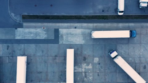 Aerial top view of a of semi-trailer truck traveling through the parking lot of the warehouse/ storage building/ loading area