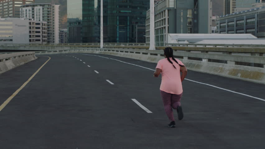 Overweight woman running resting exhausted after difficult cardio exercise tired black female in urban city at sunrise   Shutterstock HD Video #1017906676