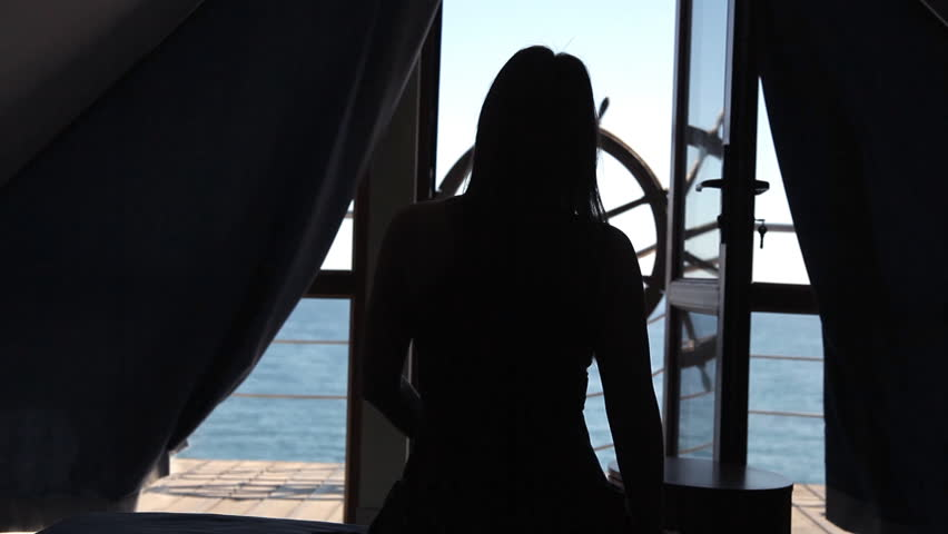 A young girl woke up in a room and looks at the terrace overlooking the sea #1017958696