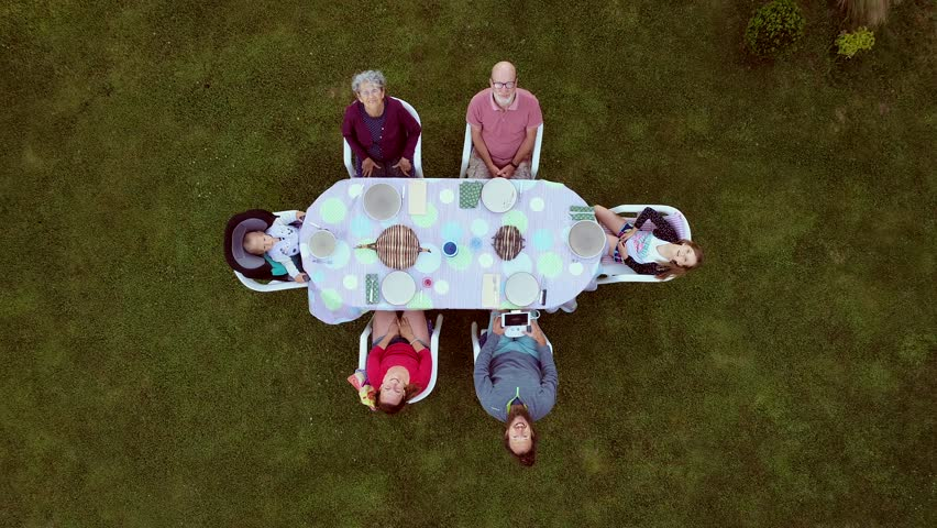 Aerial view of extended family at garden table for lunch. | Shutterstock HD Video #1017985726
