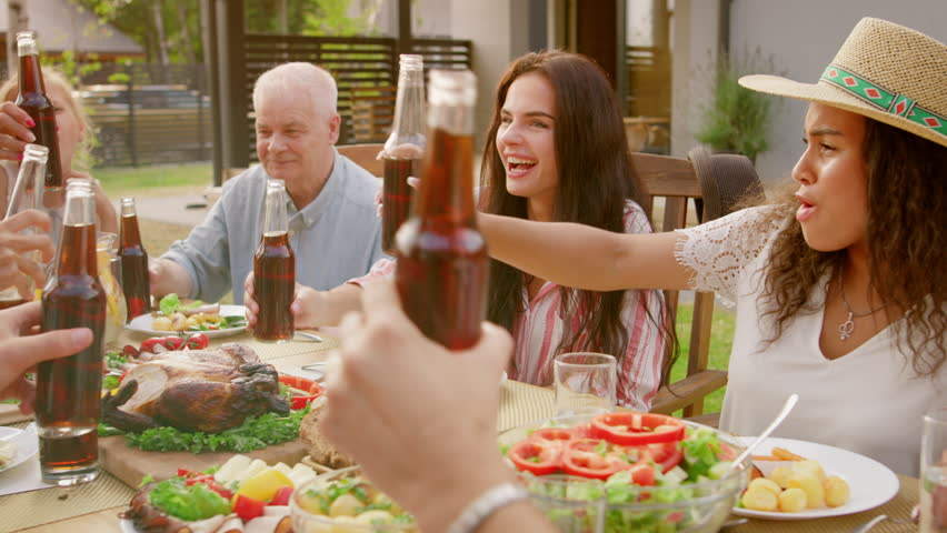 Family and Friends Gathered Together at the Table Raise Glasses and Bottles To Make a Toast and Clink Glasses. Big Family Garden Party Celebration. | Shutterstock HD Video #1018014586
