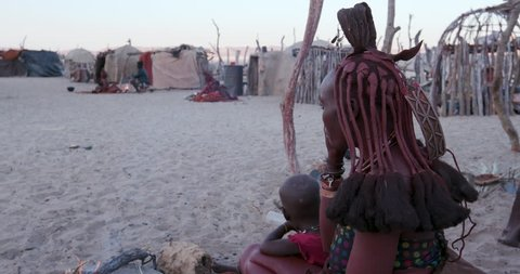 4K side view of Himba woman in traditional dress with young child, sitting and smoking outside their hut within their small compound, Namibia