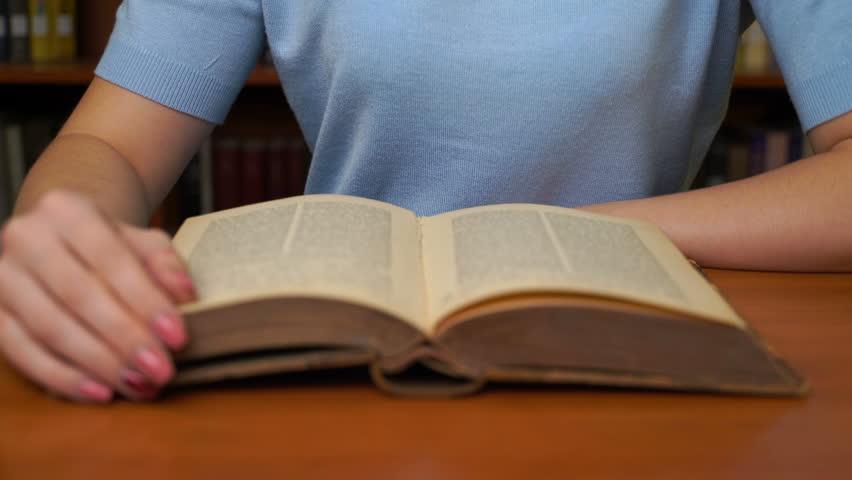 Footage pretty woman read book in library office. 4k education video | Shutterstock HD Video #1018037386
