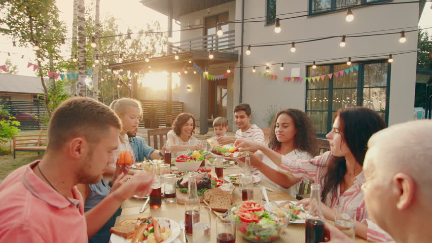 Big Family Garden Party Celebration, Gathered Together at the Table Relatives and Friends, Young and Elderly are Eating, Drinking, Passing Dishes, Joking and Having Fun. Top Down Camera Shot. | Shutterstock HD Video #1018050826