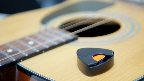 Guitarist takes a mediator or plectrum from an acoustic guitar