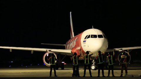 UBON RATCHATHANI, THAILAND - DECEMBER 28, 2015: Thai AIrAsia Airbus A320-200 make left tune taxi to departure to Don Mueang Airport passing airline staff that make bye bye wave to aircraft.