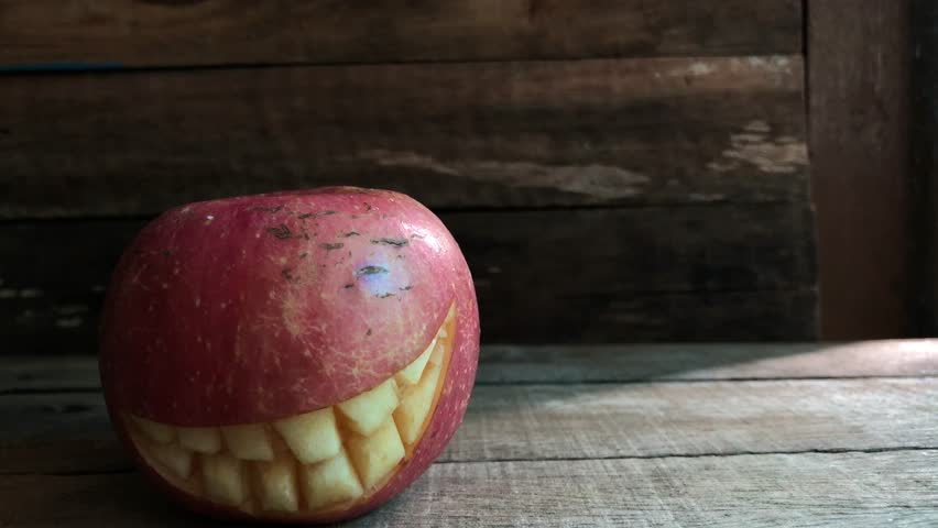Red Apple with smiling face like the pumpkin for Halloween festival, on old wood, with dark tone, rural style. Decorative with carve fruits, with space for text.   Shutterstock HD Video #1018149616