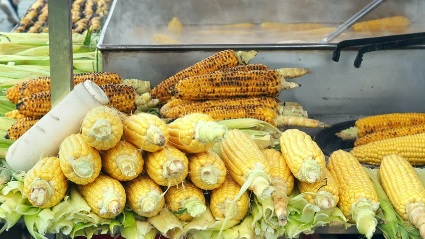 Corns stands with some more boiled and roasted corns together in the background. | Shutterstock HD Video #1018189396
