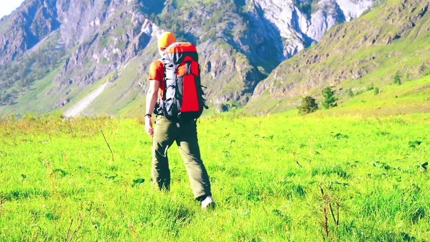 FHD Hiking man walking on green mountain meadow with backpack. Tourist travelling in sunny outdoors. Summer sport and recreation concept. | Shutterstock HD Video #1018195306
