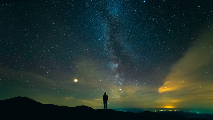 The male standing on the background of the starry sky above the city. time lapse #1018208566