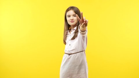 Funny child girl wearing a dress against an orange background showing number two, symbol of counting, concept of mathematics, confident and cheerful