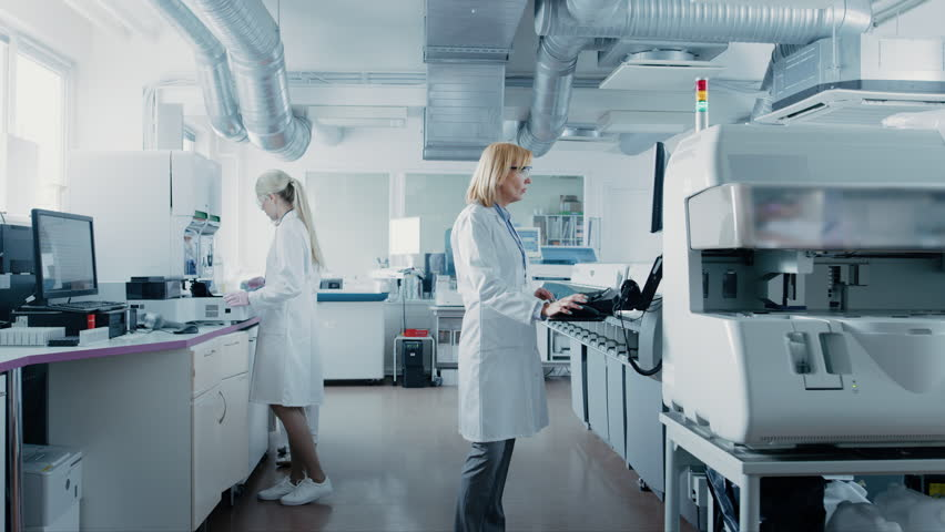 Team of Research Scientists Working On Computer, with Medical Equipment, Analyzing Blood and Genetic Material Samples with Special Machines in the Modern Laboratory. | Shutterstock HD Video #1018346236