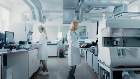 Team of Research Scientists Working On Computer, with Medical Equipment, Analyzing Blood and Genetic Material Samples with Special Machines in the Modern Laboratory.