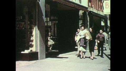 1950s: Older boy and younger boy hold hands, look both ways, cross street. Boys walk past women on sidewalk. Young kids play on playground, teens walk bike through playground.