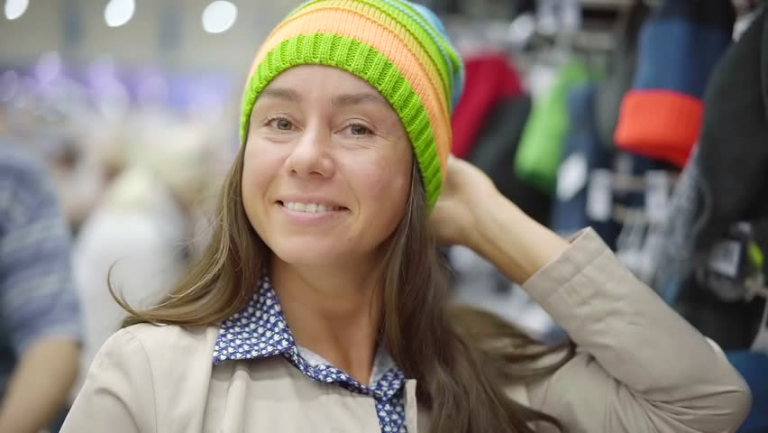 smiling female shopper is demonstrating bright knitted hat on her head in a hall of clothing store