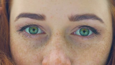 Freckled face of red haired woman with green eyes extreme close-up blink slow