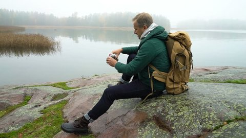 A middle-aged man with backpack sitting on a rocky shore of the Sea. Drinking coffee from a thermos and enjoying a misty autumn morning. Slow motion