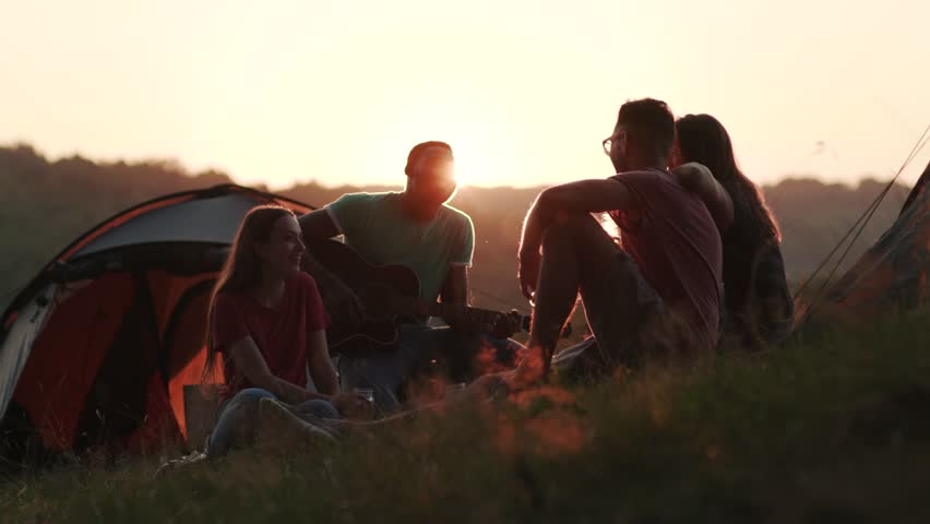 Silhouette of four friends on sunset light, actively communicating and laughing by their tourist tents. True friendship, adventure time, leisure. Camping, hiking, tourist concept