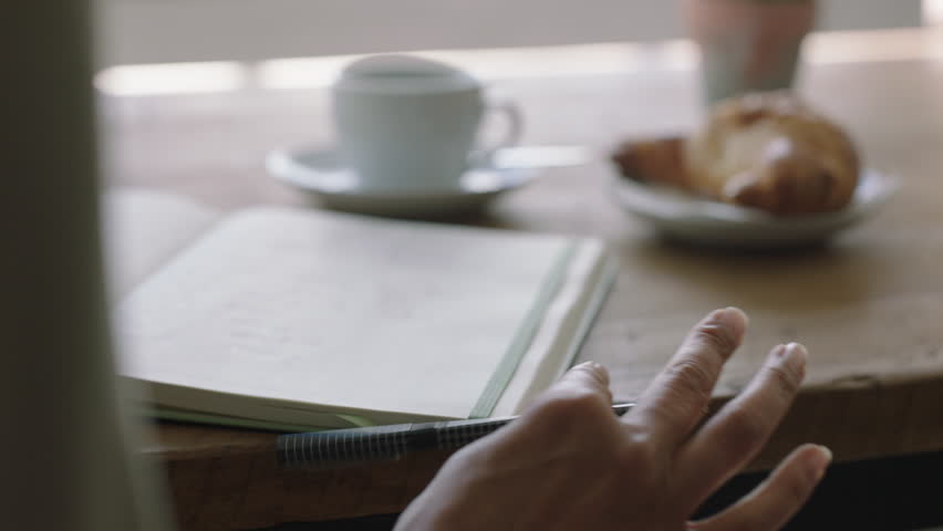 Young woman hands writing to do list making notes in diary planning using journal reminder in coffee shop close up
