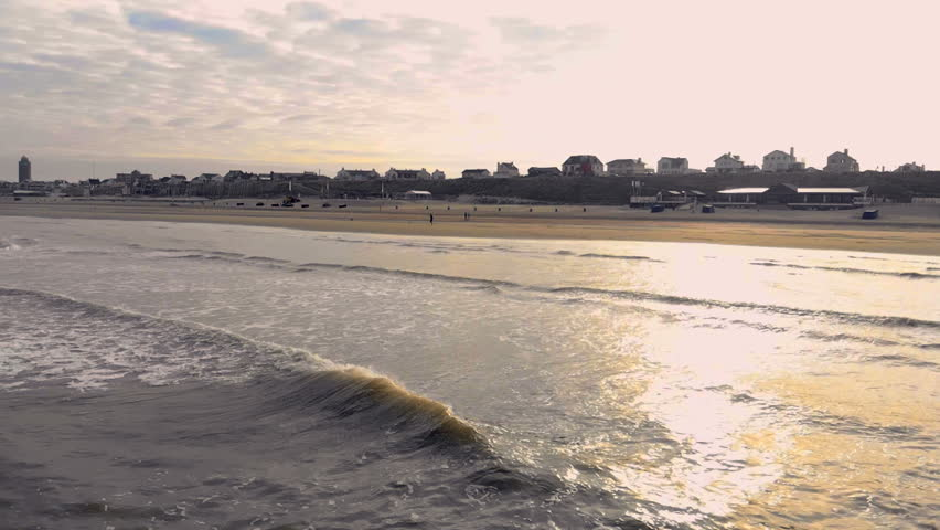 Wave moves towards the shore in the backdrop of a backyard sun. Netherlands Zanvoort | Shutterstock HD Video #1018537156
