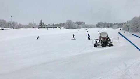 Ski instructor stops young skier on skiing downhill at winter day. Ski training on slope near snow canon in ski resort. People on ski trail. Winter sport with skiers learning riding down on piste