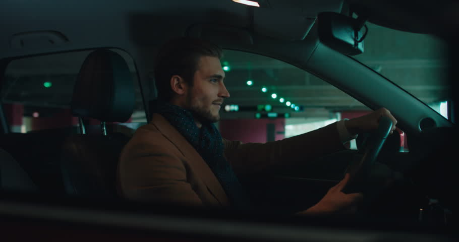 Young adult stylish Caucasian male enjoys his brand new SUV inside a covered parking garage. 4K UHD