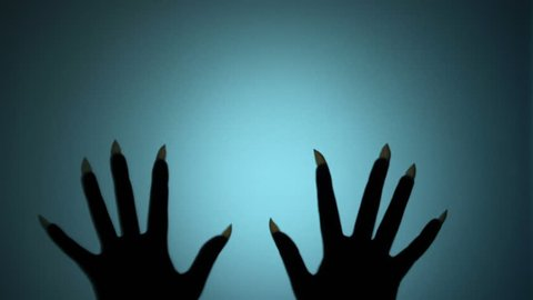 Witch hands with long sharp nails scratching glass, horrifying scene, creepiness. Blood-chilling horror thriller shot