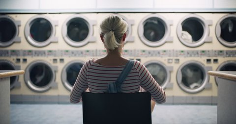 Young woman sitting in a chair with earbuds and watching the laundry machines running in interior small laundromat with bright interior lighting. Wide to Medium shot on 4k RED camera on a gimbal.