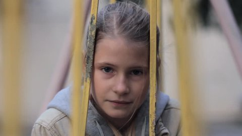 Sad depressed girl on swing looking at camera. Close up portrait of upset child sitting on playground outdoors.