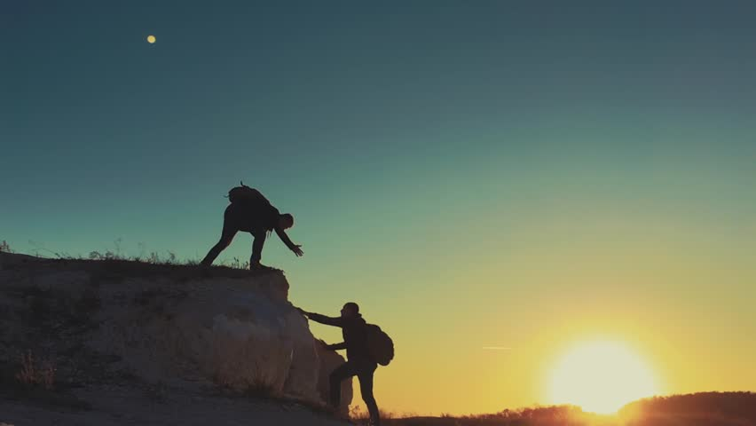 Silhouette of helping hand between two climber. two hikers on top of the mountain, a man helps a man to climb a sheer stone. couple hiking help each other silhouette in mountains with sunlight. | Shutterstock HD Video #1018647556
