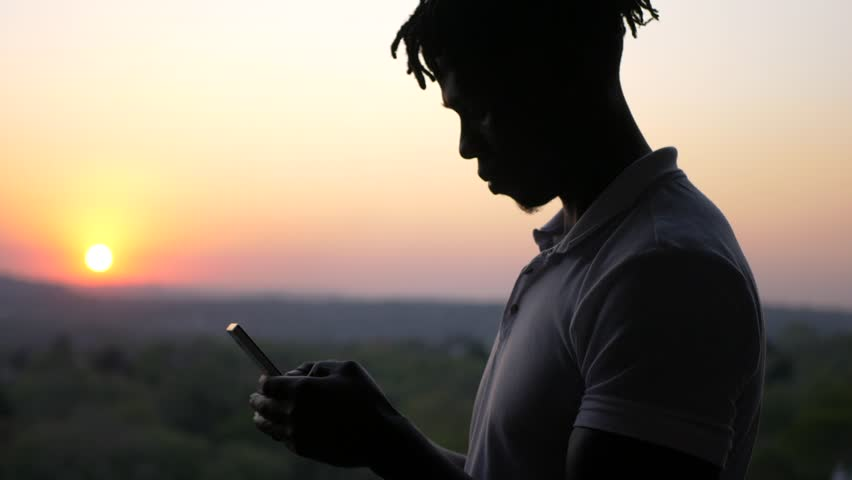 A South African young black man texting on his mobile smartphone telephone cell phone. | Shutterstock HD Video #1018664356