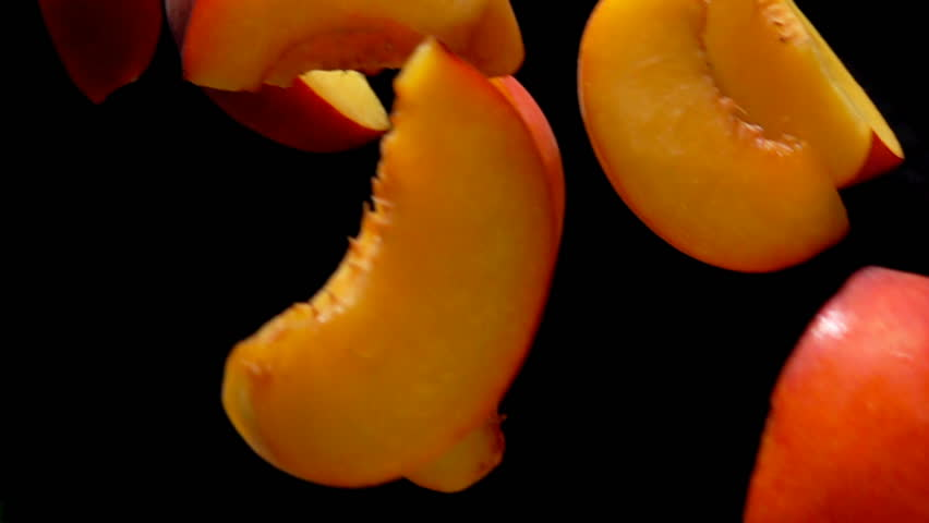 Slices of peach fly close-up on black background in slow motion | Shutterstock HD Video #1018664566