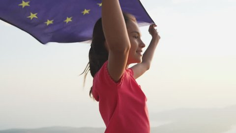 Child girl teenager is running with EU flag at sunset. European symbolic