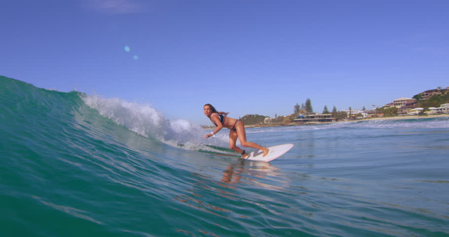 Athletic blonde woman surfing a large ocean wave and having fun in Australian beach with bright day lighting. Wide shot on 4k RED camera.