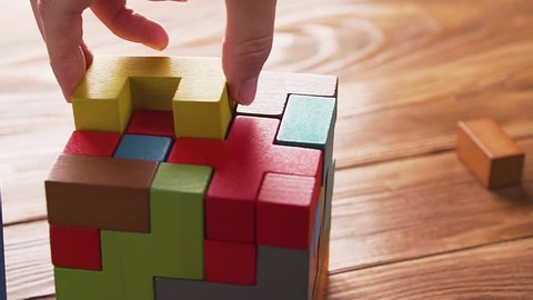 Hand folds colorful wooden cube puzzle on the brown table background, close up, dolly shot. Concept of decision making process, logical thinking. Geometric shapes on a wooden background.