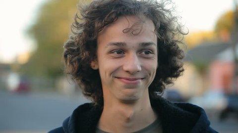 handsome cheerful boy standing on the street, defocused bg