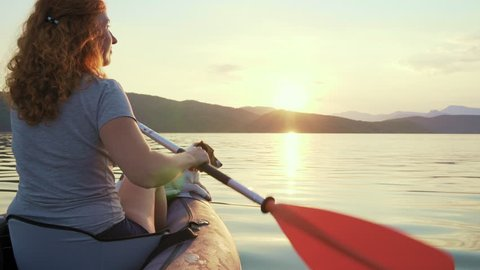Slow motion happy young woman with her dog Jack Russell Terrier paddling on an inflatable kayak on the water of a large mountain lake against a beautiful orange sunset. Family Sports Weekend