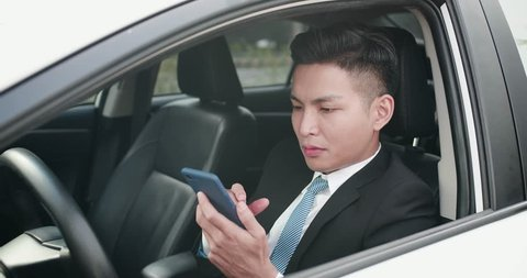 business man use a phone seriously in the car
