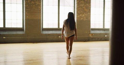 Asian dancer in industrial wood windowed studio dances during daytime. Wide to long shot on 4K RED camera.