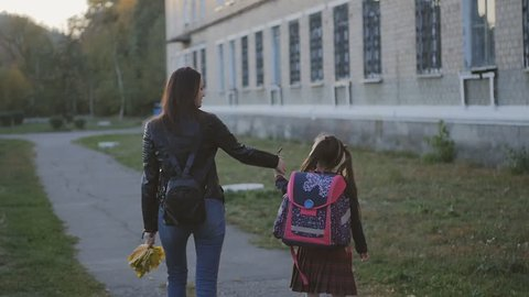 Happy mother with her daughter in school uniform go home. Mom and daughter are walking along the alley along the school. Slow Motion Sunset