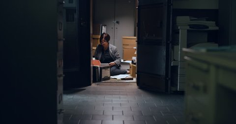 Professional woman going through files on the floor of closet in interior lawyer office with dark interior lighting. Wide to Medium shot on 4k RED camera.